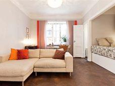 طراحی داخلی آپارتمان یک اتاقه گرم و راحت به همراه پنجره های رنگارنگ و کف پوش چوبی